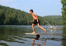 Mergulho asiático feliz do menino no lago Imagem de Stock Royalty Free