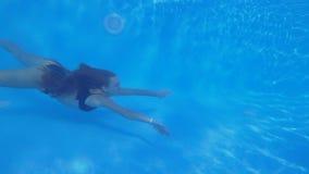 Mergulho da associação, fêmea nova de cabelos compridos no roupa de banho que flutua debaixo d'água na piscina azul clara durante filme