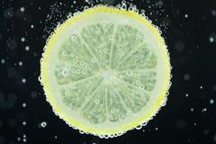 Mergulho da fatia do limão na água Imagens de Stock