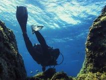 Mergulho do homem através do mar azul próximo do fundo do mar imagens de stock royalty free