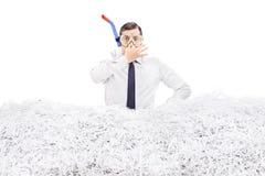 Mergulho do homem de negócios em uma pilha do papel shredded Fotografia de Stock
