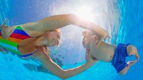 Mergulho feliz da mãe subaquático com a criança pequena na piscina fotografia de stock royalty free