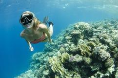 Mergulho livre da mulher e snorkeling em um recife de corais imagens de stock