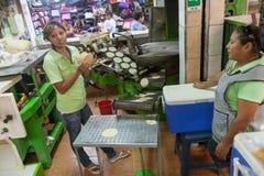 Merida kvinnor gör majs- eller havretortillor på en lokal marknad in Royaltyfri Foto
