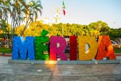 merida mexico Färgrika Merida undertecknar in den stora plazaen San Ildefonso domkyrka i aftonen Den mexicanska flaggan fladdrar  Arkivfoto