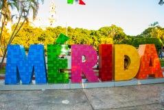 merida mexico Färgrika Merida undertecknar in den stora plazaen San Ildefonso domkyrka i aftonen Den mexicanska flaggan fladdrar  Fotografering för Bildbyråer
