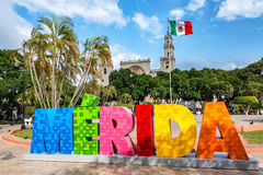 Merida Sign and Cathedral. MERIDA, MEXICO - FEBRUARY 21: Colorful Merida sign with a Mexican flag and cathedral in the background in Merida, Mexico on February Royalty Free Stock Image