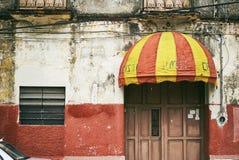 Merida/Yucatan, Messico - 1° giugno 2015: La vecchia tenda con il supporto rosso e giallo di colore alla porta della costruzione  fotografia stock