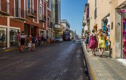 Merida-Yucatan-Mexico-april-2019: Toeristen die op stadsstraat lopen met zeer kleurrijke gebouwen royalty-vrije stock afbeelding