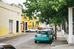 Merida/Yucatan, Mexico - Juni 1, 2015: De gröna bilarna som parkerar på streen av staden av Merida med den färgrika gula byggnade arkivbild