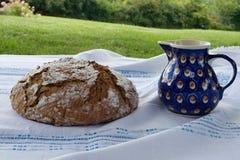 Meriende en el campo con pan hecho en casa recientemente cocido con el jarro de leche 2 Fotos de archivo