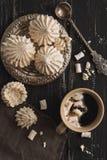 Meringe und Kaffee mit Eibisch auf einem dunklen rustikalen Hintergrund Die Ansicht von oben, flache Lage stockfoto