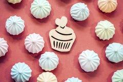 Meringen in den Pastellfarben mit hölzerner Zahl des kleinen Kuchens auf magentarotem Hintergrund Stockbilder