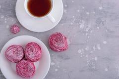 Meringen und heißer Tee der Schale auf grauem Hintergrund Stockfoto