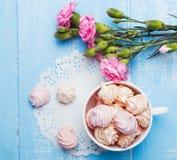 Meringen und rosa Blumen auf dem Tisch, Draufsicht lizenzfreie stockfotos
