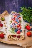 Meringerolle mit Beeren und Pistazien Stockbilder