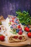 Meringerolle mit Beeren und Pistazien Stockfotos