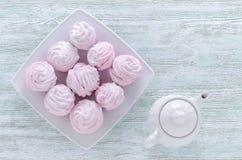 Meringhe adorabili della rosa del pastello, zefiri, caramelle gommosa e molle e una caffettiera sulla tavola d'annata di legno Immagine Stock Libera da Diritti