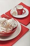 Meringhe bianche e una tazza rossa con latte. Fotografie Stock