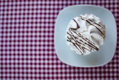 Meringue avec des rayures de chocolat sur une nappe à carreaux images libres de droits