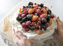 Meringue cake with berries and fruits. Hands holding a cake royalty free stock photo