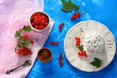 Meringue cake with fresh berries red berries currants on a blue and pink background royalty free stock photos