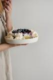 Meringue cake Pavlova in female hands Royalty Free Stock Photos