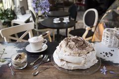 Meringue cake, vintage spoons and forks, dessert and coffee on the background of a vintage cafe stock photo