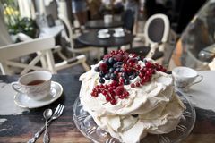 Meringue cake, vintage spoons and forks, dessert and coffee on the background of a vintage cafe royalty free stock images