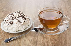 Meringue with chocolate in saucer, cup of tea and spoon Stock Images