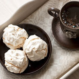 Meringue cookies and cup of aromatic coffee Royalty Free Stock Images