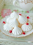 Meringue cookies. Plate of meringue cookies and a cup of tea on a tray Royalty Free Stock Photos