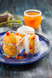 Meringue with ice cream of sea buckthorn on a blue plate on a dark wooden background Royalty Free Stock Photos