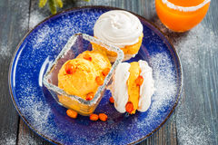 Meringue with ice cream of sea buckthorn on a blue plate on a dark wooden background Stock Photo