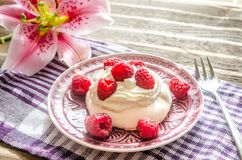 Meringue with fresh raspberries. On the wooden table Stock Photography