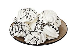 Meringue Kisses. Soft, white meringue candy with chocolate icing on a plate isolated on white Stock Image