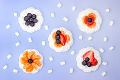 Meringue and marshmallow with berries on a lavender background. Top view royalty free stock image