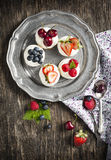 Meringue Nests topped with whipped cream with fresh berries Royalty Free Stock Photography