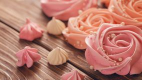 Meringue pale pink in the shape of a rose or flower. meringue is a lot of cake decoration. Close-up royalty free stock images