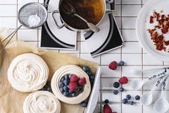Meringue for Pavlova. Fresh baking meringue for Pavlova dessert with berries, sugar powder and caramel over white tiled kitchen table. Flat lay Royalty Free Stock Images