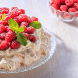 Meringue Pavlova  with whipped cream and fresh raspberries. Meringue Pavlova  with whipped cream and fresh raspberries, selective focus Royalty Free Stock Photos