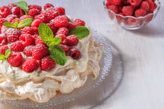 Meringue Pavlova  with whipped cream and fresh raspberries. Meringue Pavlova  with whipped cream and fresh raspberries, selective focus Royalty Free Stock Images
