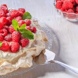 Meringue Pavlova  with whipped cream and fresh raspberries. Meringue Pavlova  with whipped cream and fresh raspberries, selective focus Royalty Free Stock Image