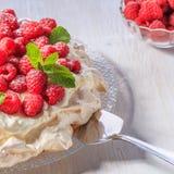 Meringue Pavlova  with whipped cream and fresh raspberries. Royalty Free Stock Image