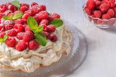 Meringue Pavlova  with whipped cream and fresh raspberries. Stock Photos