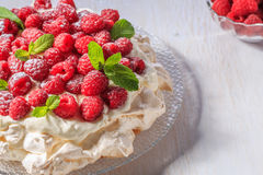 Meringue Pavlova  with whipped cream and fresh raspberries. Meringue Pavlova  with whipped cream and fresh raspberries, selective focus Stock Photography