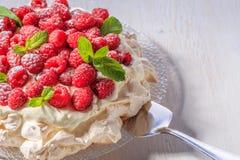 Meringue Pavlova with whipped cream and fresh raspberries. stock photo