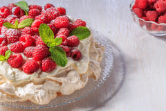 Meringue Pavlova  with whipped cream and fresh raspberries. Meringue Pavlova  with whipped cream and fresh raspberries, selective focus Stock Images