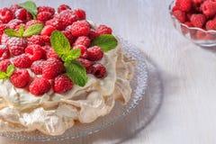 Meringue Pavlova  with whipped cream and fresh raspberries. Stock Images