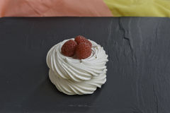Meringue with Raspberry. On black stone Royalty Free Stock Images